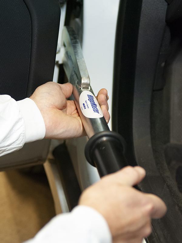 Person som använder Hingemaster. Verktyget är placerat runt dörrgångjärnet på en vit bil.